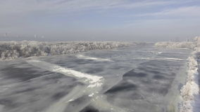 O rio congelado na floresta no inverno, a neve nas árvores, a vista do ar filme