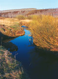 O rio corre na distância Imagens de Stock
