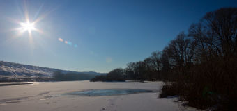 O rio do inverno coberto com o gelo e a neve em um dia ensolarado claro Foto de Stock