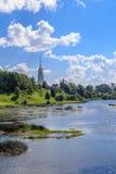 O rio flui após a costa do verde de vila com a torre de sino alta Fotografia de Stock