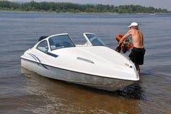 O rio, homem carreg o colete salva-vidas ao barco branco foto de stock