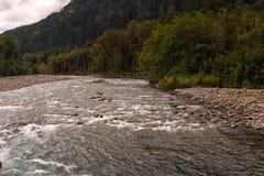 O rio raso de fluxo rápido de Elwha corre sobre seixos e rochas no parque nacional olímpico, Washington State, EUA imagens de stock royalty free