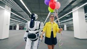 O robô alto está andando com uma jovem mulher que fala a ele vídeos de arquivo