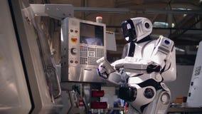O robô alto está operando uma tabuleta e um console industrial vídeos de arquivo