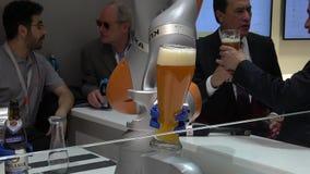 O robô de Kuka arma a cerveja de derramamento na feira de Messe em Hannover, Alemanha filme