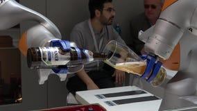 O robô de Kuka arma a cerveja de derramamento na feira de Messe em Hannover, Alemanha video estoque