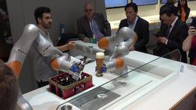 O robô de Kuka arma a cerveja de derramamento na feira de Messe em Hannover, Alemanha vídeos de arquivo