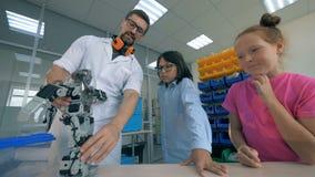 O robô do brinquedo está sendo mostrado às crianças por um especialista masculino do laboratório filme