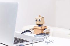 O robô está sentando-se na tabela e está funcionando-se em um portátil Fotografia de Stock Royalty Free