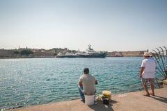 05/30/2018, o Rodes, Grécia Dois pescadores no passeio do mar de Akti Sachtouri foto de stock royalty free