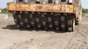 O rolo de estrada enorme com pontos está comprimindo o solo no canteiro de obras video estoque