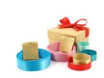 O rolo de fitas coloridas com as correias da etiqueta do papel do ouro e a caixa de presente dourada com fita vermelha curvam-se  Fotografia de Stock