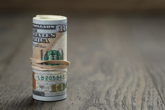 O rolo de notas de dólar novas do estilo cem está sobre Foto de Stock Royalty Free