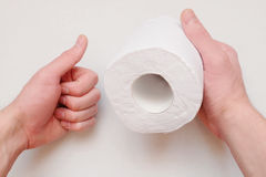 O rolo de papel higiênico nas mãos fotografia de stock