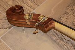 O rolo de um violoncelo composto do pegbox da porca e do close up dos Pegs que encontram-se no assoalho de telha - foco seletivo imagem de stock royalty free