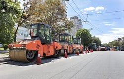 O rolo de vibração da estrada três pesada sela pronto para o reparo da estrada em uma cidade moderna Imagem de Stock Royalty Free