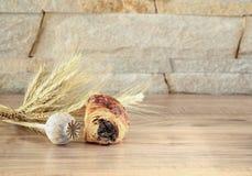 O rolo doce com papoila encontra-se em uma tabela de madeira com uma cabeça e os spikelets da papoila Fotos de Stock Royalty Free