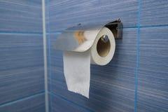 O rolo simples do papel higiênico pendura no banheiro foto de stock royalty free