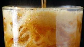 O rootbeer de derramamento da soda da cola do movimento lento misturou a água dentro ao vidro com o gelo vídeos de arquivo