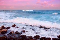 O rosa bonito matizou as ondas que quebram em uma praia rochosa no nascer do sol na costa leste da ilha grande de Havaí Fotografia de Stock Royalty Free