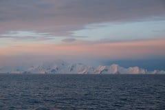 O rosa da calma da Antártica e o por do sol azul sobre a neve tamparam montanhas foto de stock