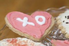O rosa e o branco gearam a cookie do Valentim do coração com as letras X Fotografia de Stock