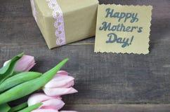 O rosa envolveu o presente com grupo do cartão do dia das tulipas e de mães na tabela de madeira Fotos de Stock Royalty Free
