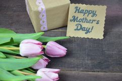 O rosa envolveu o presente com grupo do cartão do dia das tulipas e de mães na tabela de madeira Imagem de Stock