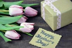 O rosa envolveu o presente com grupo do cartão do dia das tulipas e de mães na tabela de madeira Imagem de Stock Royalty Free