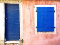 O rosa velho pintou a construção com porta azul e os obturadores azuis da janela Imagem de Stock Royalty Free
