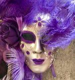 O roxo e o disfarce venetian do ouro mascaram a suspensão em uma parede fotografia de stock