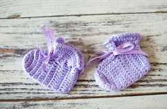 O roxo fez crochê peúgas do bebê em um fundo de madeira imagem de stock royalty free