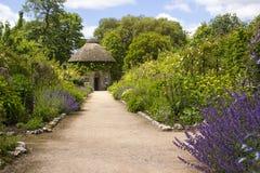 O século XIX cobriu com sapê em volta da casa cercada por camas de flor e por trajetos bonitos do cascalho no jardim murado no de imagens de stock royalty free