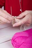 O sênior está trabalhando com agulhas de confecção de malhas Fotografia de Stock