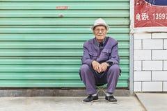 O sênior masculino senta-se fora na frente de uma porta da garagem, Duoba, China Foto de Stock