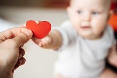 O símbolo de um coração vermelho na mão de um homem que transmite à uma criança em uma mão pequena imagem de stock