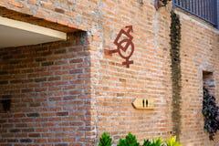 O símbolo do cargo do guia do sinal do toalete que pendura na parede de tijolo Fotos de Stock Royalty Free