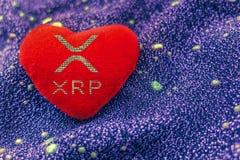 O símbolo do cryptocurrency XRP é um coração vermelho do luxuoso com um fundo de néon ripple foto de stock