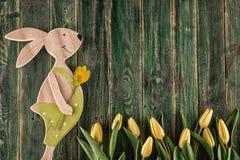 O símbolo tradicional da estação de mola gosta de tulipas e do coelho amarelos no fundo de madeira, tempo feliz de easter Fotos de Stock