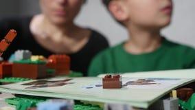 O ` s da criança entrega o jogo com os tijolos pequenos de um lego, mãos perto acima Lego é uma linha popular de brinquedos da co video estoque