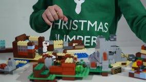 O ` s da criança entrega o jogo com os tijolos pequenos de um lego, mãos perto acima Lego é uma linha popular de brinquedos da co filme