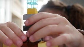 O ` s da criança entrega o jogo com os tijolos pequenos de um lego, mãos perto acima Lego é uma linha popular de brinquedos da co vídeos de arquivo