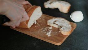 O ` s da mulher do close up entrega o corte de uma parte do pão branco na placa de madeira no fundo preto Fazendo um sanduíche video estoque