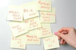 O ` s da mulher do close up entrega a vara folhas amarelas do papel da etiqueta com frases da motivação em uma placa branca Fotos de Stock