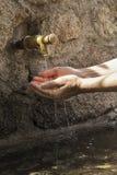 O ` s da mulher entrega a água da colheita de um bico da fonte Fotos de Stock Royalty Free