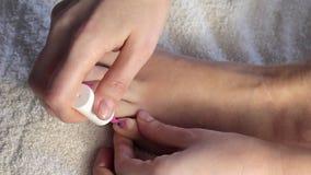 O ` s da mulher entrega as unhas do pé da pintura Menina que pinta seus pregos na laca do rosa do pé video estoque