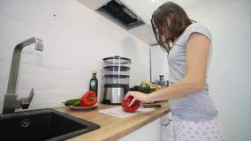 O ` s da mulher entrega o corte da pimenta de Bell vermelha doce em uma placa de corte de madeira Conceito saudável do alimento M video estoque