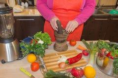 O ` s da mulher entrega o cozimento da refeição saudável na cozinha, atrás dos legumes frescos Fotografia de Stock