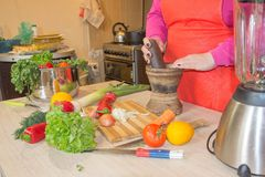 O ` s da mulher entrega o cozimento da refeição saudável na cozinha, atrás dos legumes frescos Imagem de Stock