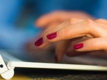 O ` s da mulher entrega a datilografia no teclado do portátil na opinião interior, lateral o homem de negócios que usa o computad Foto de Stock
